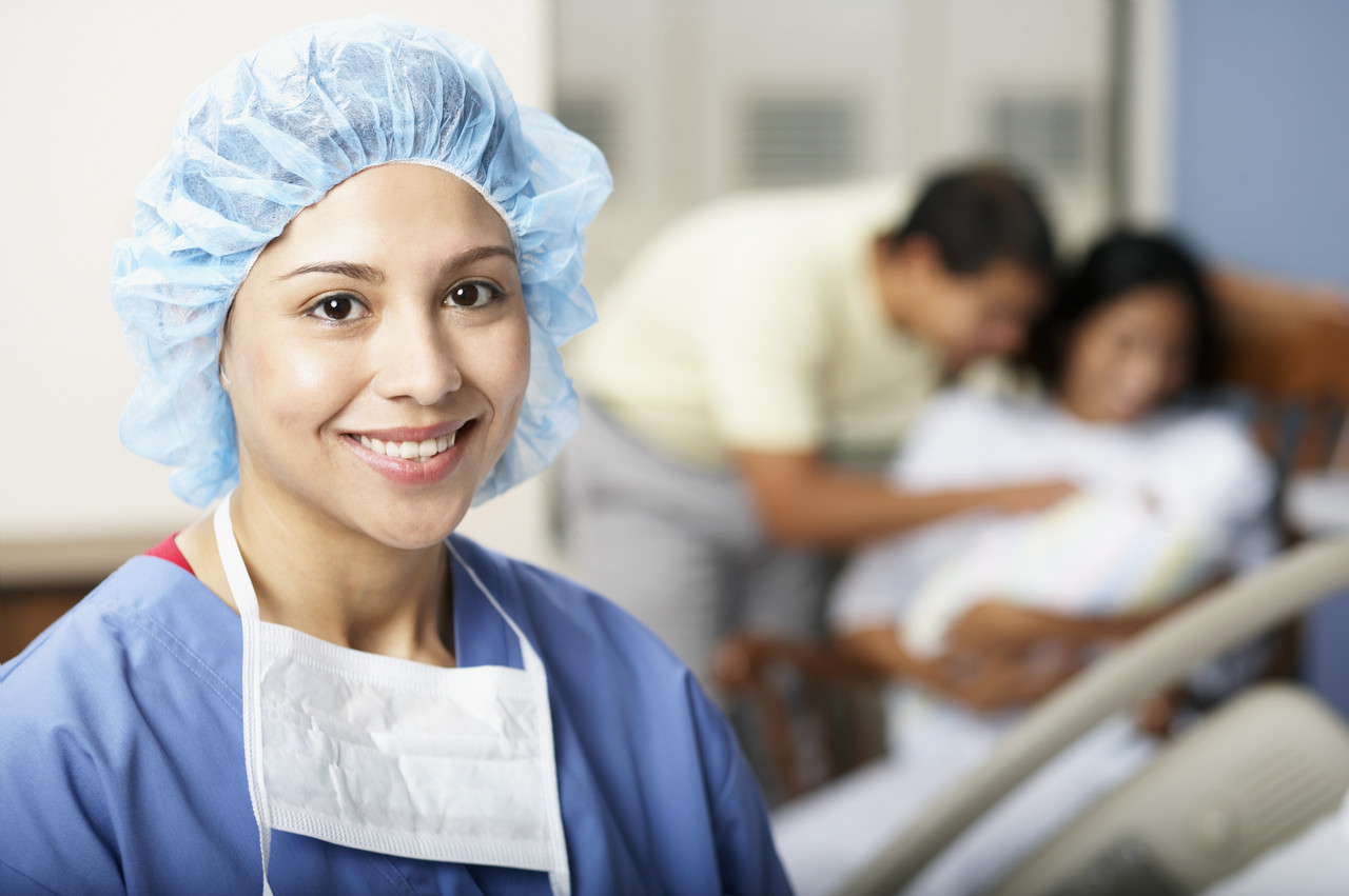 Smiling Physician near New Family --- Image by © Royalty-Free/Corbis